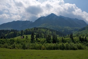 The ridge of the Piatra Craiului Mountains seen while driving back from Plaiul Foii into Zarnesti on a lovely summer day. Above them there are some white clouds blocking part of the sun.